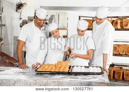 Team Of Baker's Analyzing Breads At Table