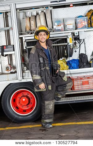 Confident Fireman Standing By Truck At Station