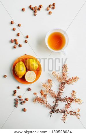 Lemons on a plate surrounded by orange hazelnuts on a white background. Flat lay