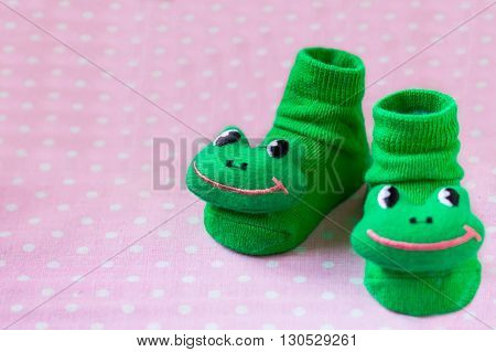 Pair of green child socks with frogs toys closeup on spotted pink background, selective focus