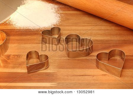 Cookie Cutters, Rolling Pin & Sifted Flour on Cutting Board
