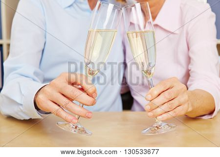 Old couple clinking glasses of champagne for celebration
