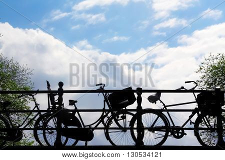 Silhouette of bicycles parked on a bridge, blue cloudy sky background