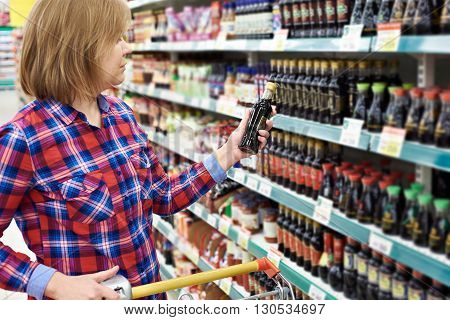 Woman With Soy Sauce In Store