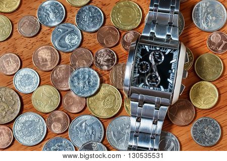 Men's wrist watch on metal coins as in time is money concept
