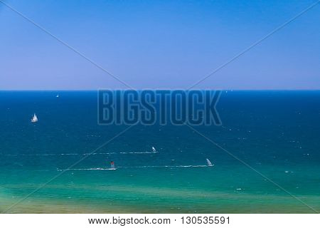 Sea landscape with sailing ships and windsurfers