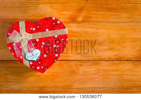 Gift box with heart shape with inscription i love you on wooden background