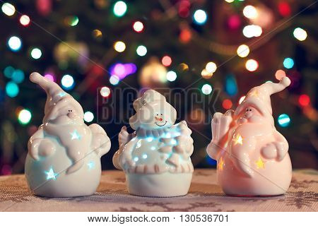 Illuminated Snowman and Jack Frost (Santa Claus) dolls in front of Christmas tree lights that are defocused, blurred background