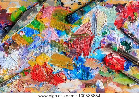 Colourful oil paint, different types of brushes and palette knife on palette