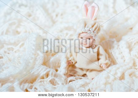 Ceramic doll newborn baby on patterned background