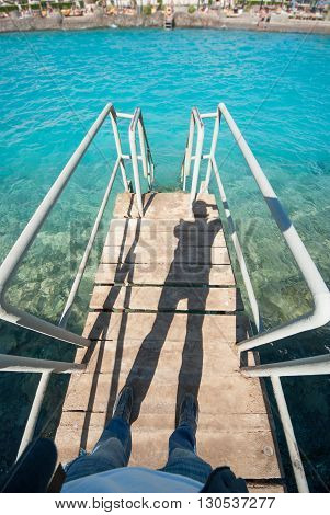 Old vintage metal wooden stairs leading to blue turquoise sea water from beach. Beautiful summer day. Swimming pool with grunge retro stairs on the ocean coast. Top POV, Point of view shot.