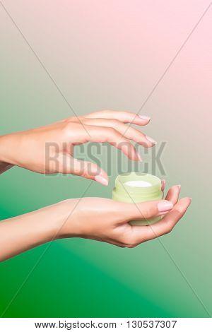 Female manicured hands holding cream jar isolated