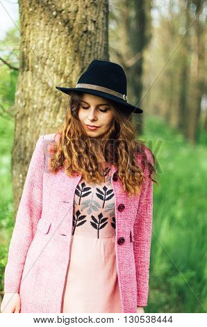Portrait young elegant woman in pink coat and black hat. Fashion outdoors shot street style concept. Blogger outfiit. Spring portrait of stylish model posing in the park