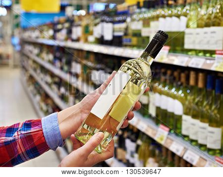 Woman With Bottle Of White Wine In Store