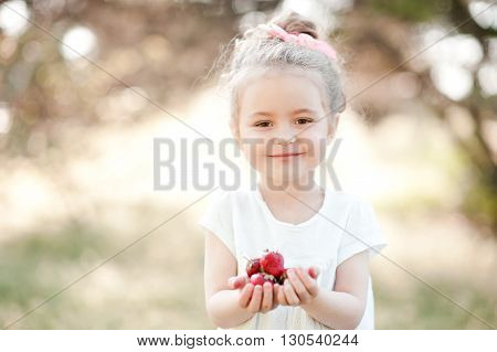 Cute kid girl 4-5 year old eating strawberries outdoors. Looking at camera. Childhood. Summer season.