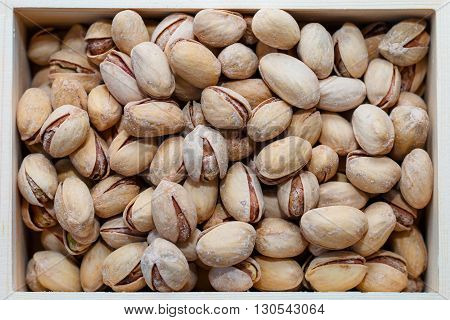 Pistachio nuts in a shell, salty, roasted in a wooden box