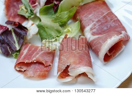 closeup of slices of rolled cured pork ham jamon with lettuce