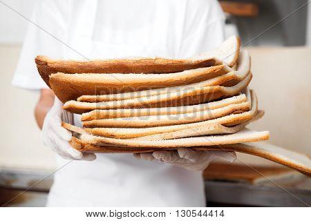Baker Holding Bread Waste In Bakery