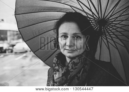 Middle-aged, tired woman under an umbrella. Street Photography.