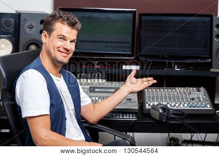 Confident Man Showing Monitors On Audio Mixing Table