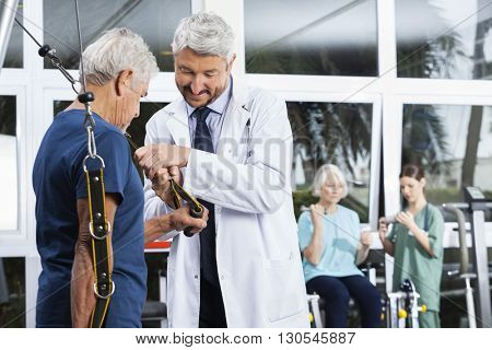 Doctor Assisting Senior Man With Resistance Band