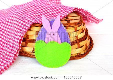 Easter egg and Bunny, basket, towel on white wooden background. Felt crafts