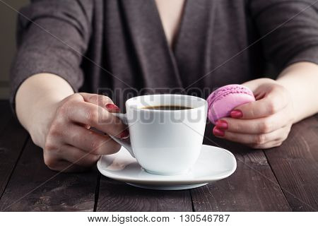 Coffee And Macaron Cookies On Table In The Morning, Female Hand Holding Cup With Hot Beverage