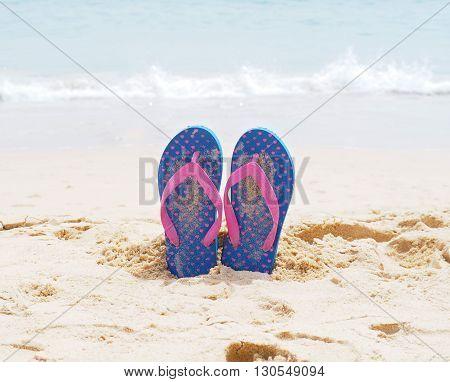 Blue flip flop on summer sand beach