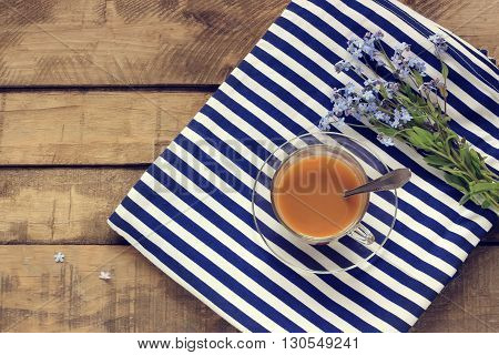 The theme of a holiday at sea top view. A Cup of coffee a vest and a forget-me-not on a wooden platform. Table-still life. Empty space for Your text.