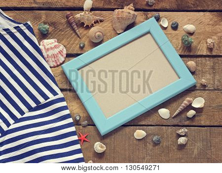 Marine still life top view. The theme of the holiday. Shells photo frame and sea vest on a wooden platform.