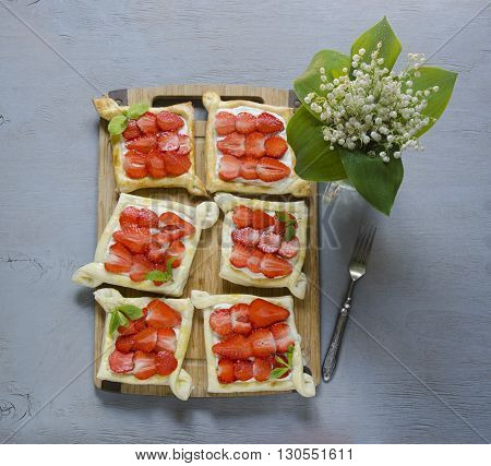 strawberry puffs on the wooden table, sweet morning with spring flowers