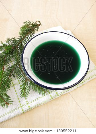 Green spruce needles medicinal bath in bowl