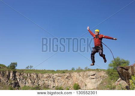 Man jumping off a cliff with a rope on a sunny day.