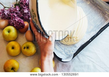 A woman prepares a pie apple tree the ingredients for the cake: flour egg vanilla sugar milk sour cream soda. The girl in the kitchen. Women's hands. Preparation of Desserts for breakfast