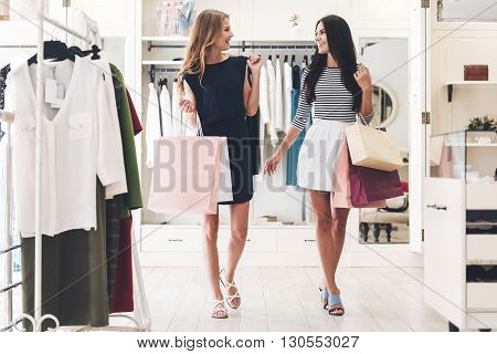 Great day for shopping. Two beautiful women with shopping bags looking at each other with smile while walking at the clothing store