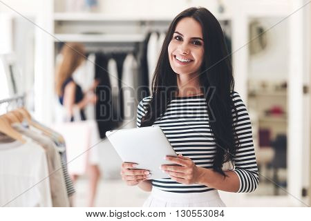Starting new business. Beautiful young woman holding digital tablet and looking at camera with smile while standing at the clothing store