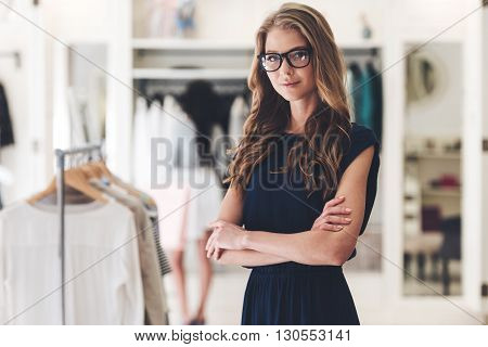 Confident in her business. Beautiful young woman in glasses keeping arms crossed and looking at camera while standing at the clothing store