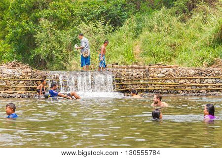 PAI, THAILAND - April 13, 2016 : Many people swimming at the small weir irrigate at Wang Pla in Pai Thailand