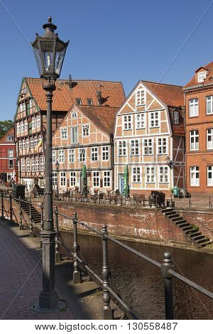 Stade, Germany - May 13, 2016: Facades of half-timbered houses at the inner harbor in the old town, old street lamp in foreground.