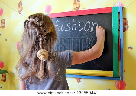 girl with nice plaits writes word Fashion on the home blackboard