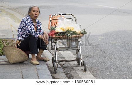 Hanoi, Vietnam - May 14, 2016: Asian vendor a cart on the street with pineapple tray and conical hat on the sidewalk of a street in Hanoi capital.