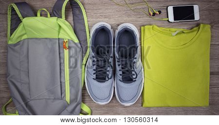 Set for sports shoes backpack t-shirt mobile phone with headphones close-up on a wooden background top view