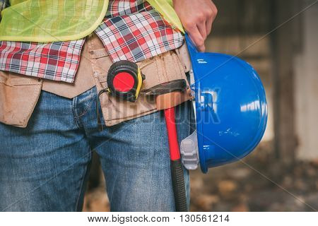 Close-up of a construction worker with blue helmet and tool belt at construction site.