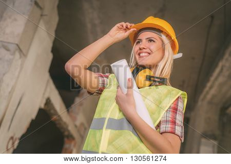 Beautiful young female construction architects at a construction site. She is holding plans and smiling holding helmet.