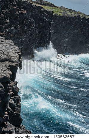 Waves crashing against the lava rocks in Big Island, Hawaii