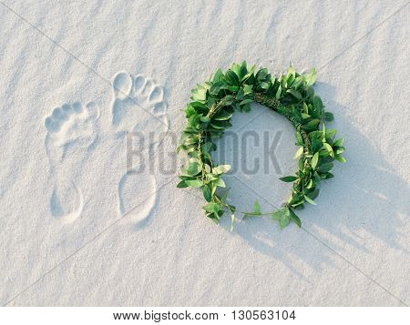 Footprint and green laurel wreath on white sand tropical beach.