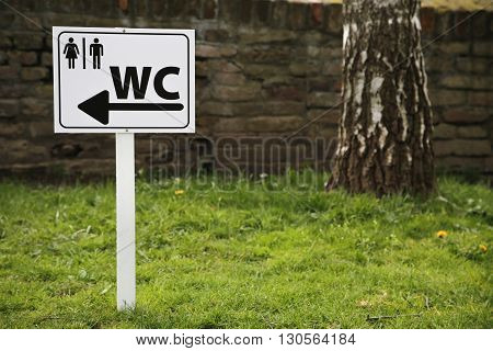 Toilet sign for man and female on white table outside in field