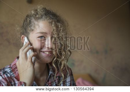 Redhead teenager talking on a mobile phone at home