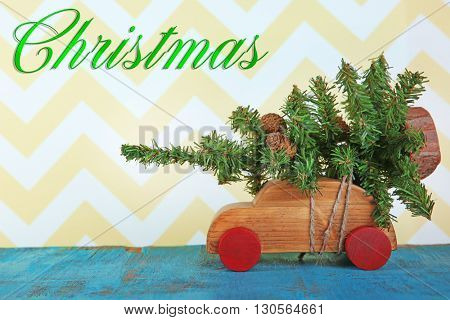 Wooden toy car with Christmas tree on a table over pattern background