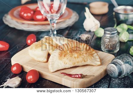 Fresh baked  pasties filled with meat and vegetables .Toned photo